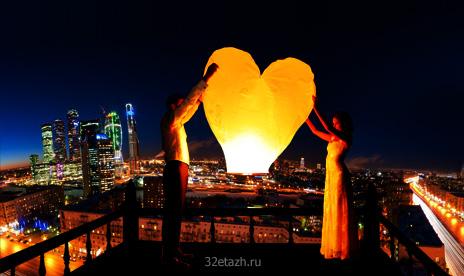 Парень с девушкой запускают фонарь желаний с крыши